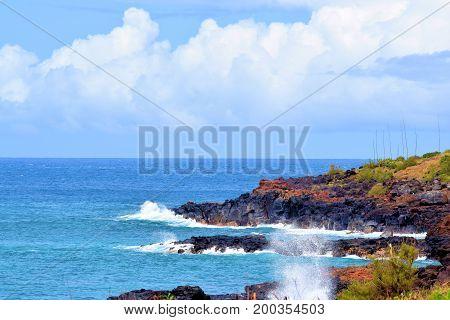 Rural and rugged Hawaiian Coast with waves crashing onto volcanic lava rocks taken in Kauai, HI