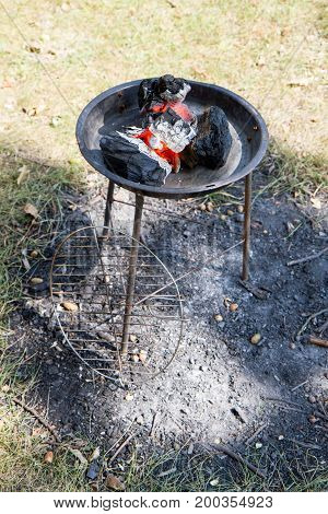 A Barbecue grill with fire going, outdoors