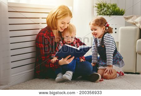 Mother reads book to children son and daughter
