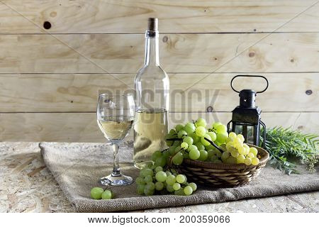 Bottles of wine, wineglass and grapes on a wood background closeup