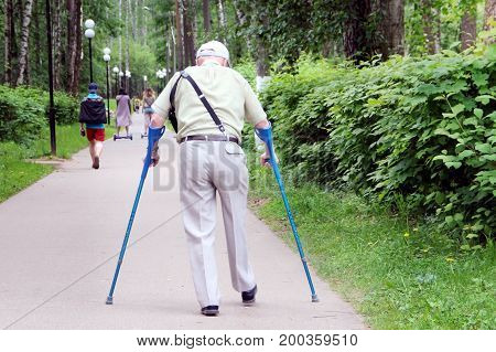Grandpa with crutches walking in the park