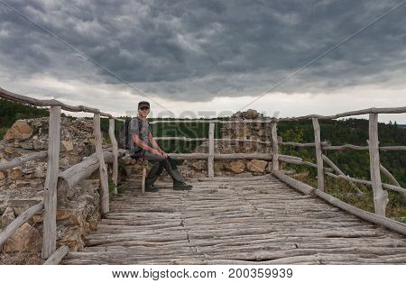 Man sitting on wooden bench on castle ruins in backgrounds is cloudy sky.