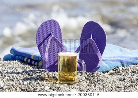 Beach accessories and a glass of beer at the sea close-up