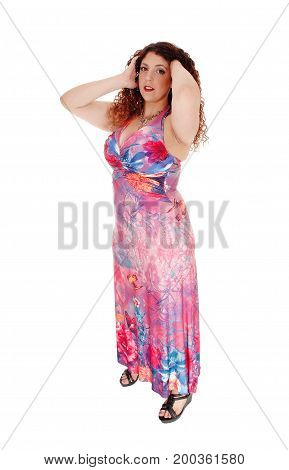 A young woman standing in a long colorful dress with curly brunette hair whit her hands on her head isolated for white background.