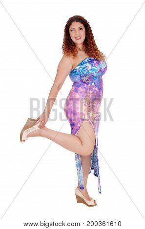 A young woman standing in a long colorful dress with curly brunette hair lifting one leg isolated for white background