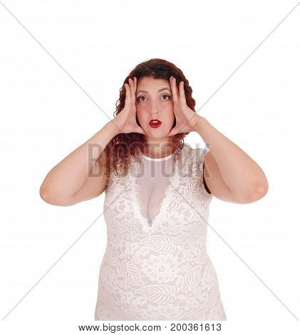 A young woman with booths hands on her face and screaming with her mouth open isolated for white background.