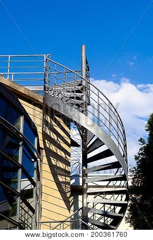 Spiral staircase on the outside of a modern building. The road in the sky.