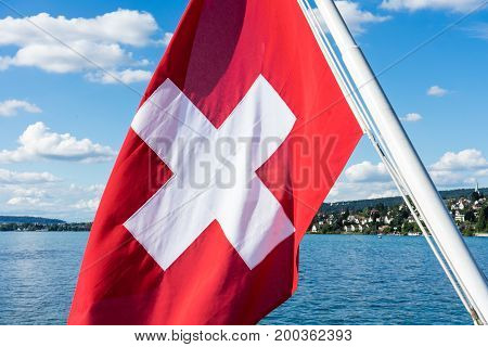 swiss national flag on lake with water and blue sky white clouds