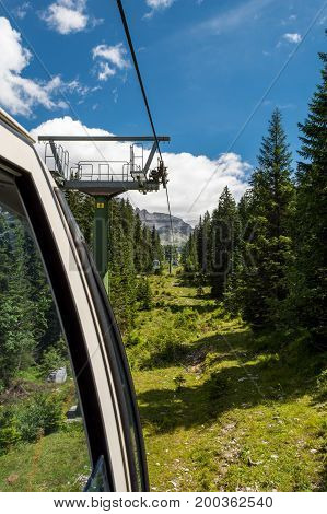 Riding a cable car through a forest. Madonna di Campiglio, Brenta Group in Italy.
