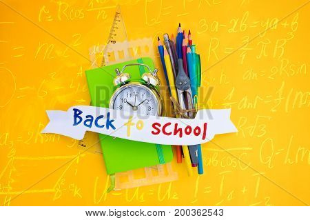 back to school concept - alarm clock and school supplies with back to school text on ribbon, top view scene with math formulas