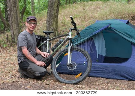 Caucasian man with his tent and mtb bike in the woods in the summer morning