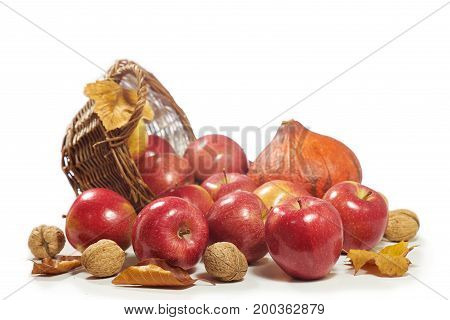Apples, nuts, pumpkin with autumn leaves isolated on white background