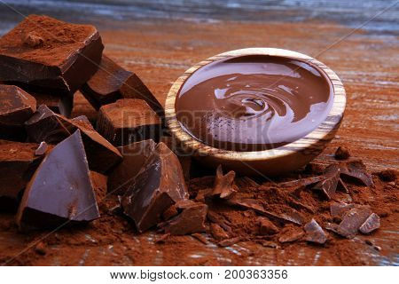 Chocolate Cream Melted, Chocolate Pieces And Chocolate Powder On Wooden Table