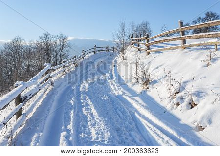 Winter Country Landscape With Timber Fence And Snowy Road