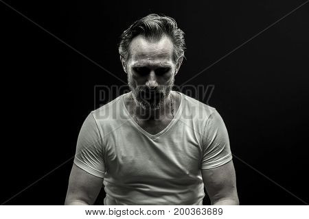 Black and white portrait of mid aged man. Male in white t-shirt on black background showing emotion of disappoinment.