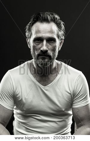 Black and white portrait of brutal beardy man. Monochrome photo of mid aged male on black backdrop.
