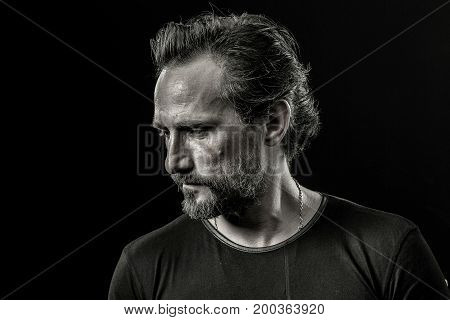 Close up portrait of a mid aged man severely looking aside. Image of a male showing emotion of disappoinment and trouble.