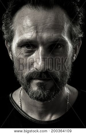 Monochrome portrait of self-confident brutal man. Close up view of male on black background.