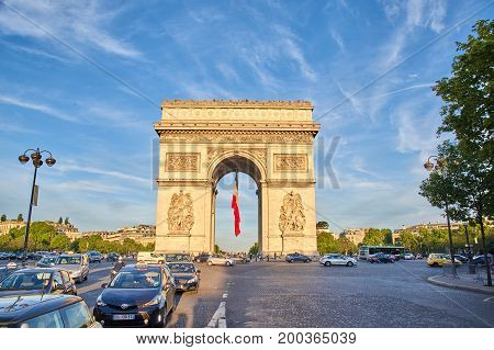 PARIS FRANCE - MAY 10 2017 : Arc de Triomphe with french flag in the evening. Triumphal Arch is one of the most famous monuments in Paris standing at the center of Place Charles de Gaull