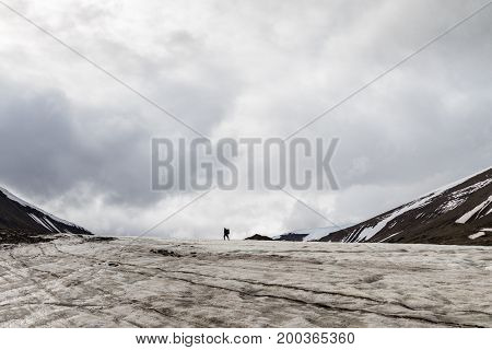 Man walking away in the distance, on a glacier in Longyearbyen, Svalbard.