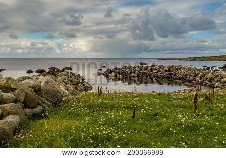 Breakwater in ocean, dramatic sky and green grass in front of beach at Lista in southern Norway