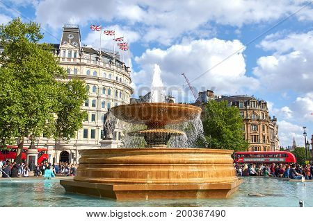 LONDON ENGLAND - MAY 13 2017 : Fountain at Trafalgar Square. The square is a public square in the City of Westminster Central London built around the area formerly known as Charing Cross