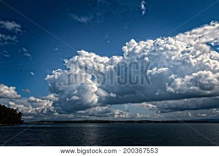White Cumulus cloud in blue sky at sea with water reflections. East Coast Australia.