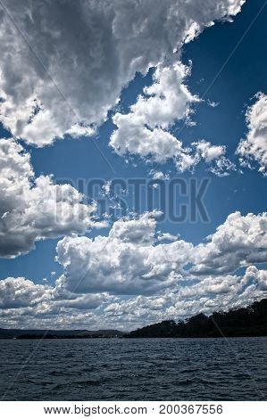 White Cumulonimbus cloud in blue sky at sea with water reflections. East Coast Australia.
