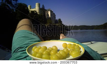 Grapes on plate above a man's legs overlooking lake and castle.