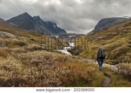 Hurrungane In Jotunheimen, Norway, with Store Skagastoeltind as the highest peak. This is Norways third highest mountain, and is also known as Storen. Man walks alone along the waterfall towards the mountains
