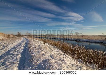 Winter landscape with snow, river, common reed, blue sky, road with snow, sunshine. Norway, Fredrikstad, Nature Reserve. This is an important area for birds and bird watchers in Norway.