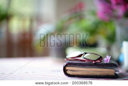 Diary and glasses on a table with a blurred background