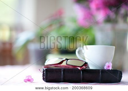 Diary cup and glasses on a table with a blurred background