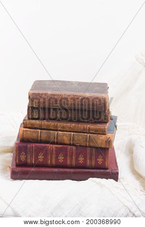 Pile of old aged books on romantic lace background