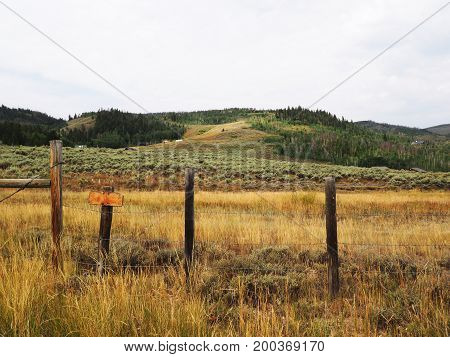 A wire fence on a prairie in Colorado. In the back are gently rolling hills.