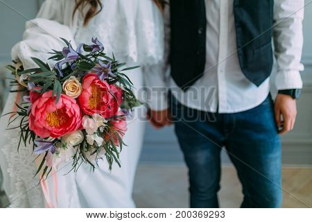 Bride Holds In Hands A Rustic Wedding Bouquet With White Roses And Crimson Peonies On Window Backgro