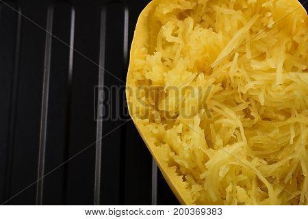 Closeup on a roasted spaghetti squash on a black baking sheet