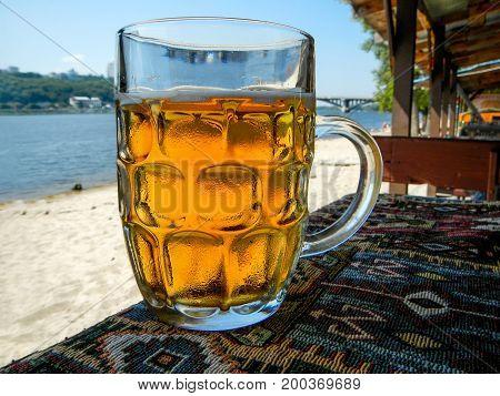 Cold beer mug with handle on table