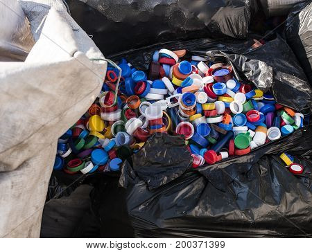 Pile of plastic bottle caps waiting to be recycled.
