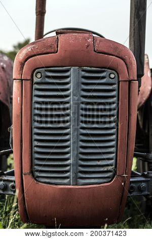Red old tractor front part metal grill.