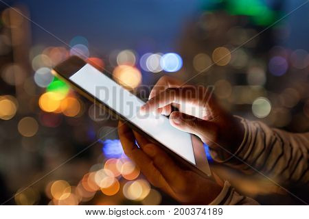 hand using digital tablet on night beauty light bokeh in city