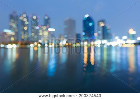 Blue tone blurred bokeh light office buildng waterfront abstract background