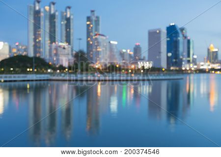Twilight city blurred bokeh light with water reflection abstract background