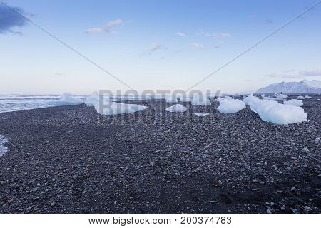Breaking Ice from glaciaer on small black rock sand beach Iceland winter season landscape background