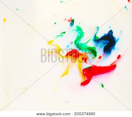 Food Coloring in milk. Food coloring in whole milk creating bright colorful abstract backgrounds. Colorful chemical experiment.
