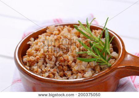 saucepan of cooked buckwheat on checkered dishtowel - close up