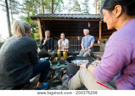 Friends Talking While Having Food By Firepit In Forest