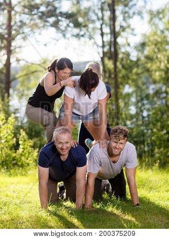 Happy Coworkers Making Human Pyramid On Grassy Field
