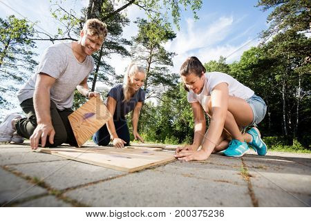 Happy Male And Female Friends Solving Wooden Planks Puzzle