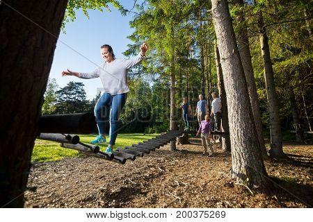 Friends Watching Woman Crossing Log Bridge In Forest